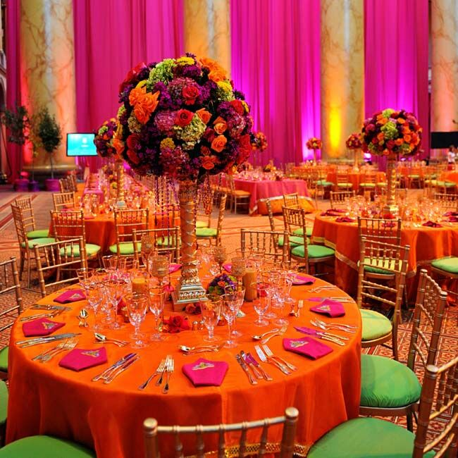 A mixture of round and rectangular tables featured tightly-packed spheres of saffron, burgundy and fuchsia blooms. The fragrant globes sat atop regal candelabras with beads draping down for extra glamour.