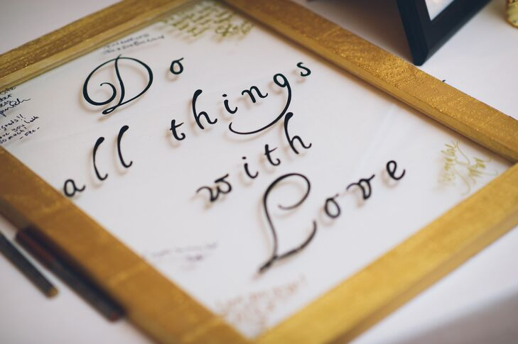 "The couple welcomed all 125 guest into their ceremony with the help of a unique guest book. Gold-framed glass served as just that with the words ""do all things with love"" printed along the front. Friends and family members stopped to write their names, well wishes and notes around the design."