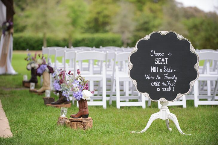 Their aisle decor took the theme to a new level. Wooden posts were spaced along the burlap runner and topped with vintage cowboy boots. Each one was filled with wildflowers, purple hydrangeas, purple lilies, greenery and white roses. A flameless candle inside a mason jar also highlighted the accent atop its own wooden post.