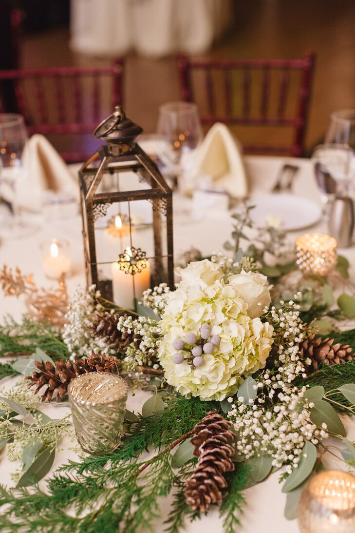 Katie warmed up her winter wedding decor with lanterns and candelabras on every table. The centerpieces also incorporated flowers from her bouquet, like hydrangeas, baby's breath, and pinecones.