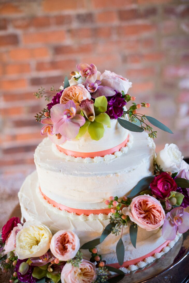 """""""Among the many beautiful reception tablescapes, our cake tables stood out as two focal points that reflected our true personalities,"""" Emily says. The wedding cake was a three-tier pound cake with peach and blackberry-raspberry filling and draped with full, fresh flowers and garden greenery."""