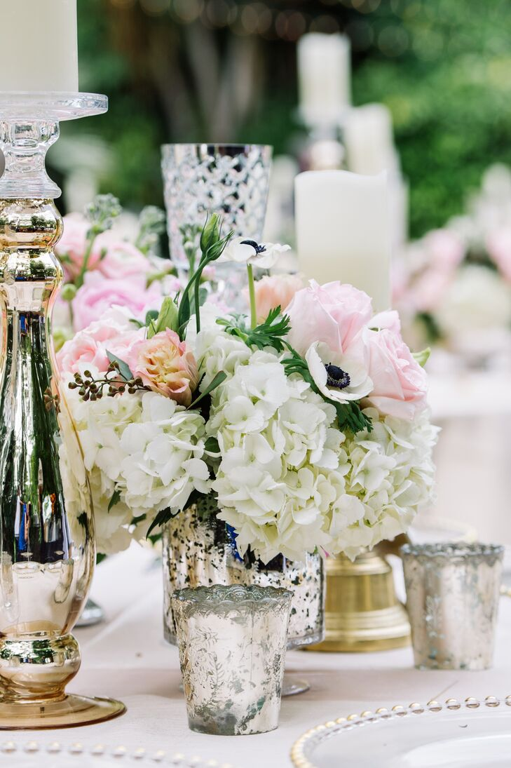 Tall candleholders were paired with short mercury glass vases filled with white hydrangea, white anemones and pink peonies.