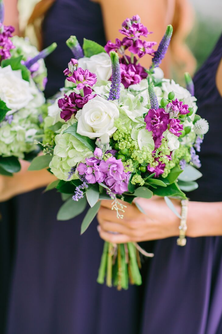 Vibrant bundles of hydrangeas, roses, veronica, eucalyptus and stock in shades of purple, green and white popped against the bridesmaids' dark purple dresses. To play up the evening's rustic aesthetic, blooms were arranged to create a textured appearance, and wildflowers were woven throughout.