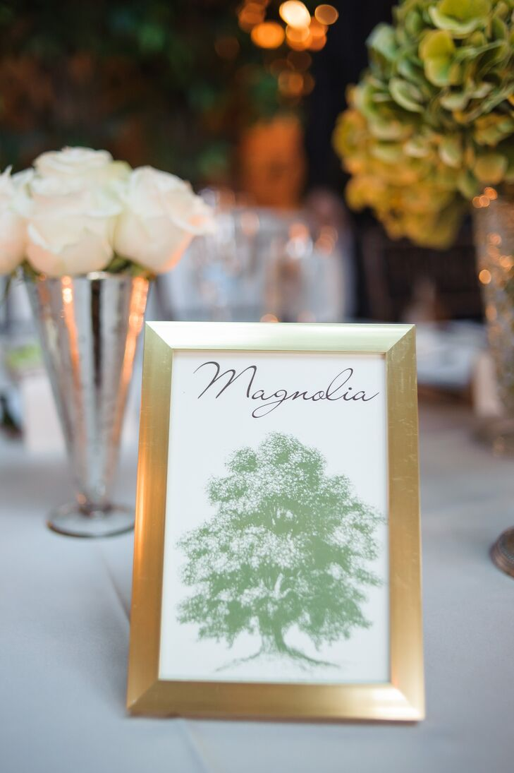 Tree-themed table numbers were framed in gold.