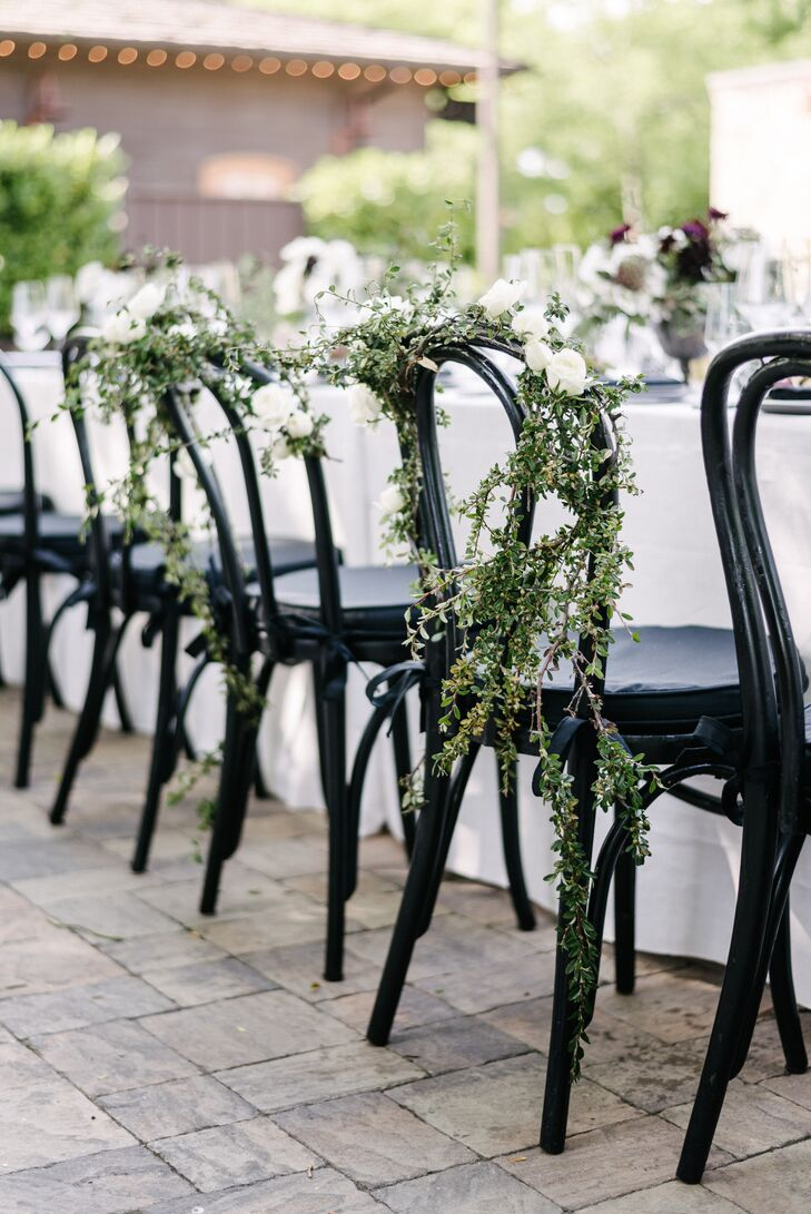 At the reception, the bride's and groom's chairs were draped with thin green vines blossoming with white flowers.