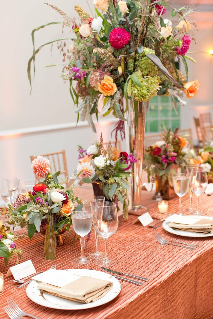Centerpieces at the reception consisted of silver vases in different shapes and sizes filled with overflowing arrangements of roses, dahlias, ranunculus, dusty miller and other flowers.