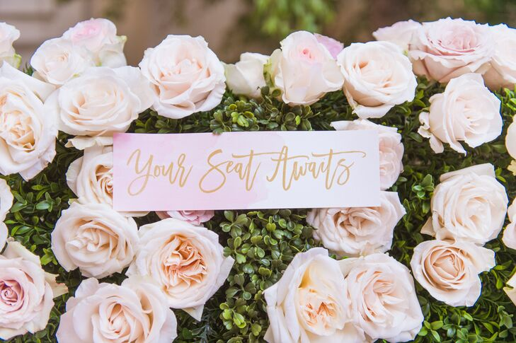 At the reception at the Four Seasons in Las Vegas, Nevada, guests found their names and seating assignments on an elaborate flower wall covered with blush and ivory roses.