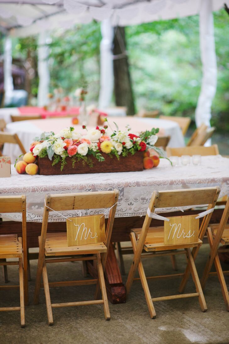 With cute Mr. and Mrs. signs hanging from Jessica and Dan's chairs, the main bridal table had a lace tablecloth runner that was made by the mother of the bride and featured a garden style floral arrangement of peonies and roses in a long wooden flower box.
