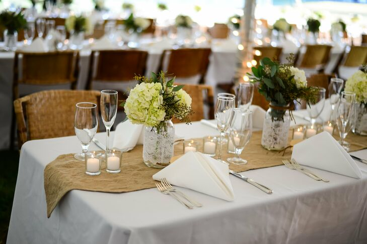 """The family-style dining tables were covered in simple white linens with tea lights and mason jars. """"I love the contrast of thick rustic fabrics mixed with touches of delicate lace, so our table runners were burlap. My  mother and I wrapped mason jars with lace and twine and filled them with hydrangeas and greens,"""" says the bride."""