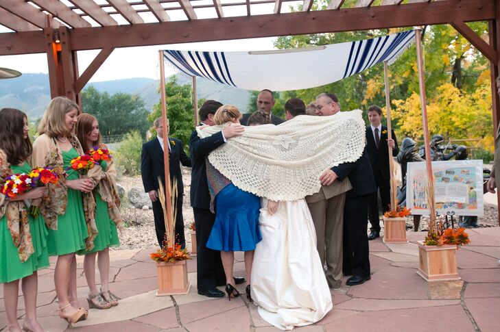 Jenny and Mark exchanged vows under a chuppah they made. They used a blue and white stripped blanket for the topped and added fall-inspired leaves around the bottom.
