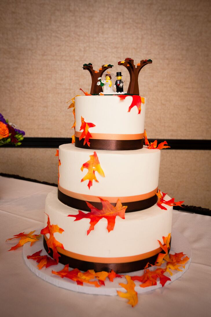 Jenny and Mark had a fall-inspired white fondant wedding cake. Each tier was wrapped with orange and brown satin ribbons and decorated with orange and yellow leaves.