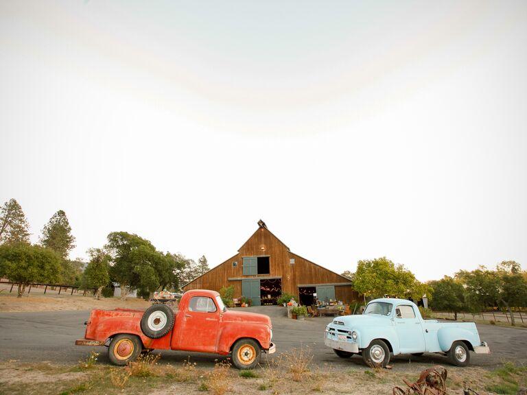 Two trucks sit outside a barn wedding venue
