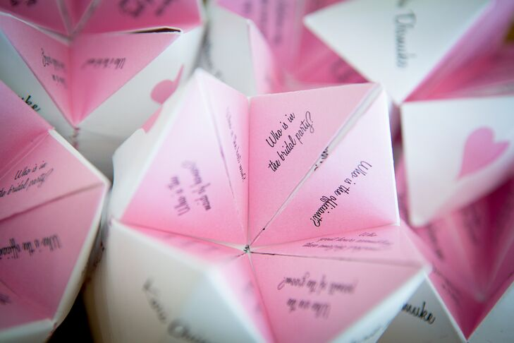 "The bride and groom made custom pink and white ""cootie catchers"" for their ceremony program, full of facts about the groomsmen and bridesmaid. They wanted their guests to become better acquainted with their wedding party during their ceremony."