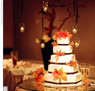 """Jonathan chose the couple's cake, a five-tiered, hexagonal cake with raspberry filling. The outside was frosted with off-white buttercream and decorated with chocolate-brown ribbon and orange lilies. """"It was definitely a crowd-pleaser!"""" Caroline says."""