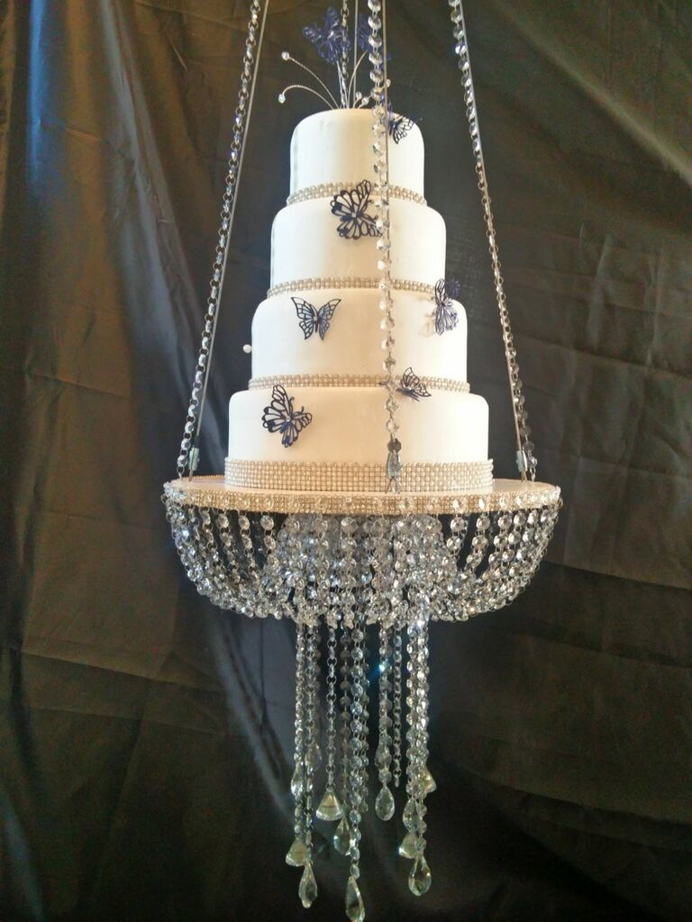 Floating chandelier wedding cake stand supporting four-tier cake