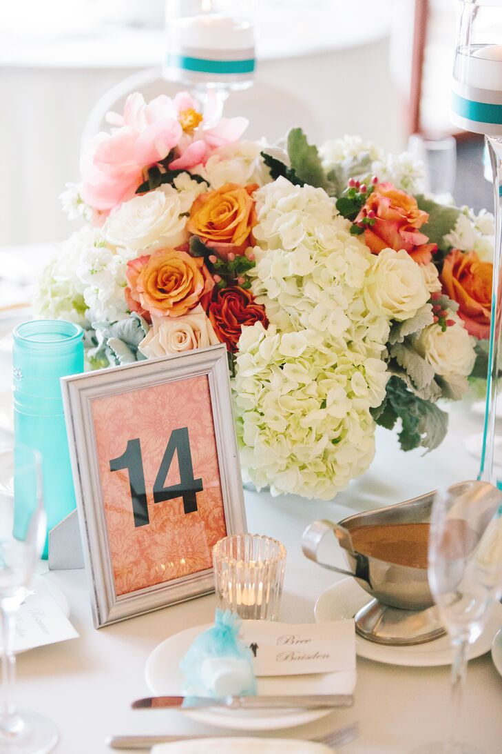 Low arrangements of white hydrangeas and coral roses were designed by Couture Flowers and decorated the tables at the reception.