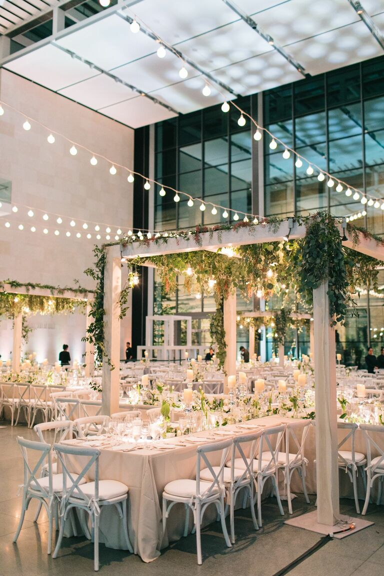 Indoor wedding reception with pergola and string lights