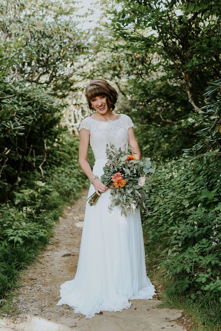 Christian carried an asymmetrical bouquet of eucalyptus accompanied by bright pops of summery color. Daisies in warm tones of orange and pink were added for a natural, bohemian aesthetic.