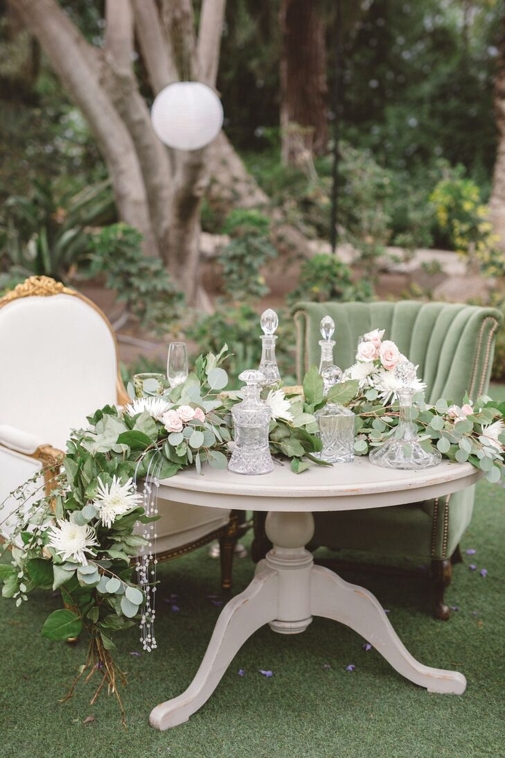 White and green lounge chairs surrounded a light wooden table draped with a long lush garland of leaves and ivory blooms, making its way around the glassware decorating the surface.