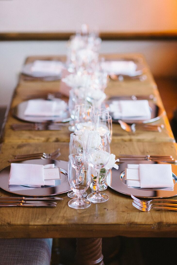 Silver chargers added a glam touch to the place settings, which sat atop rustic wood tables.