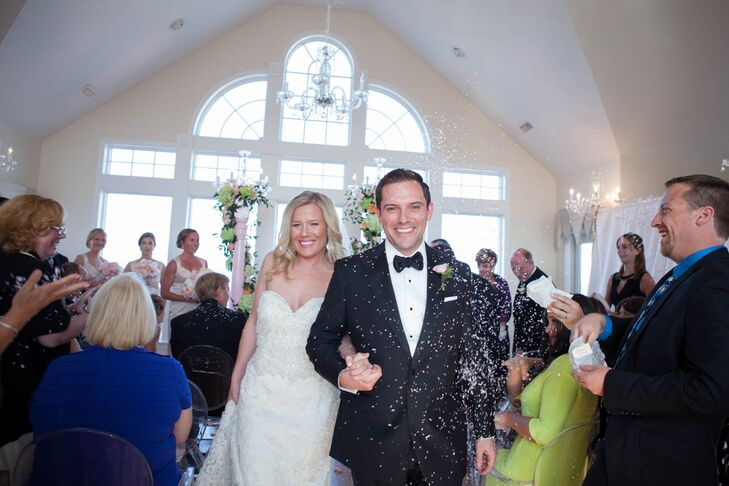 Brian wore a custom-made Brooks Brothers tuxedo for the formal seaside affair in Corolla, North Carolina. The groomsmen echoed his look with JoS. A Bank attire. The men added a little romance to their look with pink rose boutonnieres that went beautifully with the blush and peach bouquets.