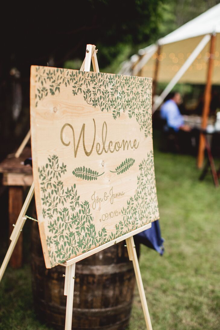 Jenna and Jon made all the decorations for the intimate woodland affair, including the wooden welcome sign at the entrance to the reception tent. To capture the organic, nature-inspired theme, the sign featured fern and vine flourishes in a soft shade of green.