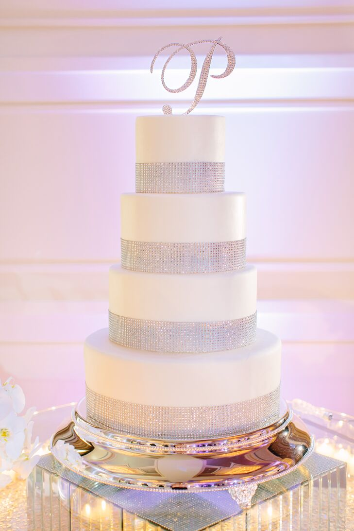 """Stephanie and Zach chose a four-tier white fondant covered wedding cake with silver rhinestones lining the base of each tier. Their rhinestone """"P"""" cake topper was found by Stephanie's mother. Baked at the Four Seasons Resort Orlando at Walt Disney World Resort, the confection was composed of both chocolate ganache cake with raspberries coulis and fraisier cake with vanilla grand marnier crème anglaise, says Stephanie."""