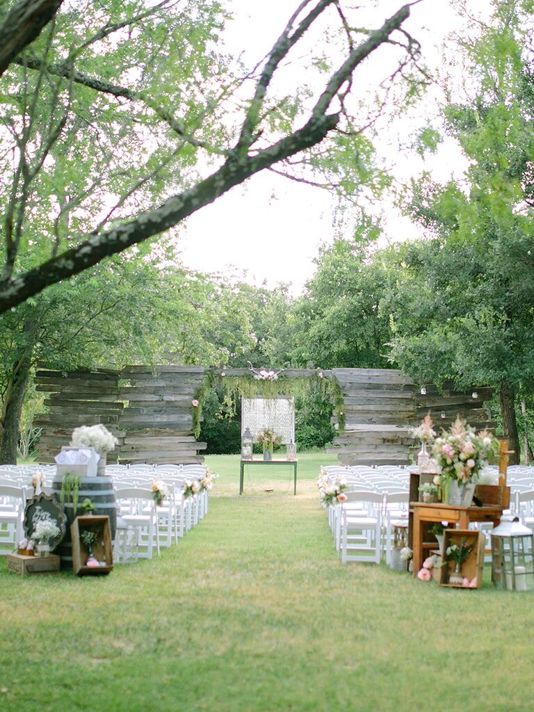 Floral decor with wooden crates and tables for an outdoor wedding ceremony