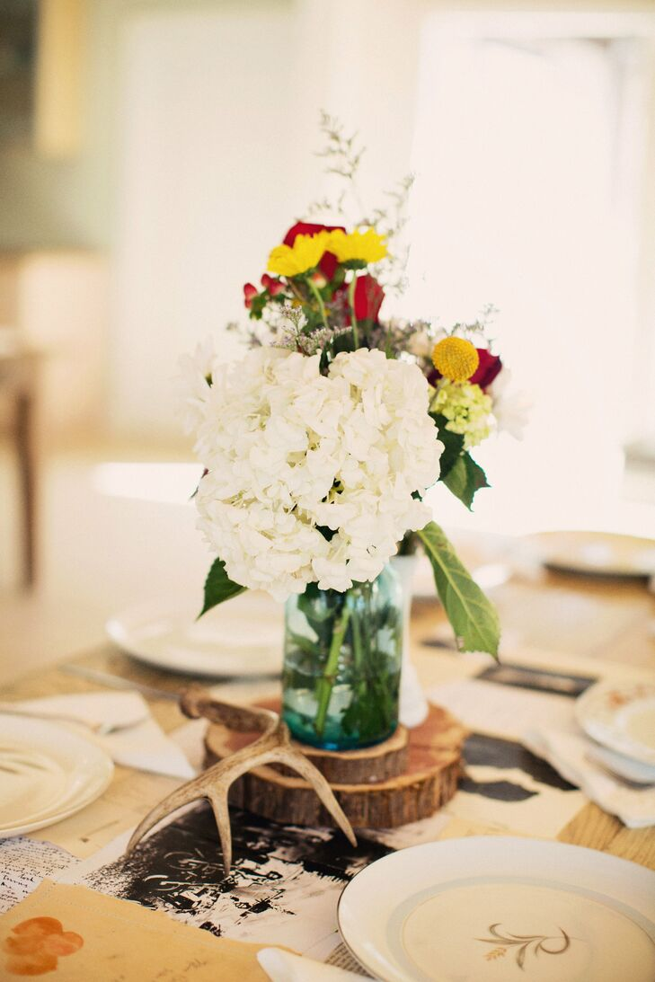 Arrangements of white hydrangeas and yellow billy balls were displayed in small glass bottles.